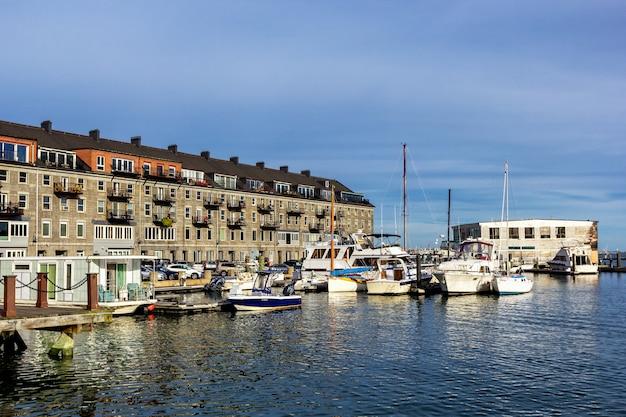 Красивый серый дом и причал с лодками и яхтами в районе норт энд в бостоне