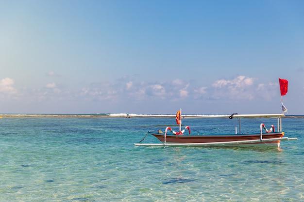 Традиционная лодка и тропический пейзаж на пляже пандава, бали