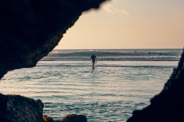 岩、バリ、インドネシアに囲まれたウルワツのビーチでサーファーの夕景