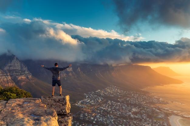 美しい夕日の景色とケープタウンのライオンの頭の山の頂上の端に立っている若い男