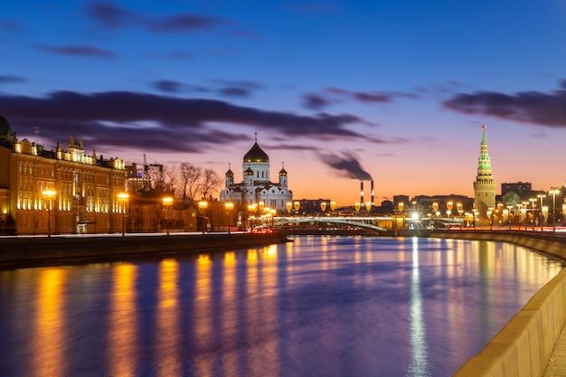 モスクワ、ロシアのクレムリンの壁と救世主ハリストス大聖堂の景色を望むモスクワ川の堤防に沈む夕日