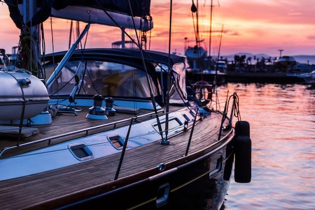 美しい夕日で海洋の木製デッキ立っているヨット
