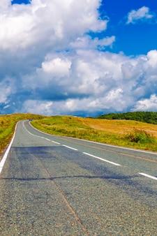 曲がりくねった田舎道と曇りの青い空