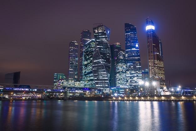 高層ビルと川に架かる未来的な橋とモスクワ市の夜景