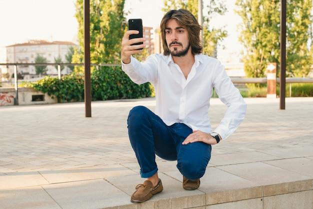 白いシャツとひげを持つ魅力的な若い男は、公園で深刻な顔をして自分撮りになります。