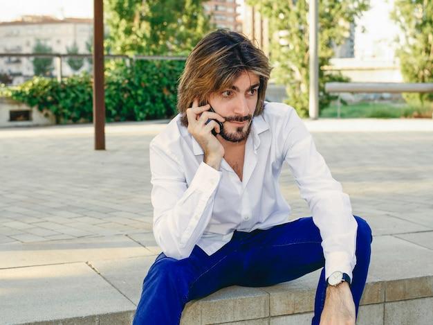 Привлекательный молодой человек с бородой, с белой рубашкой разговаривает с смартфон, сидя в парке.