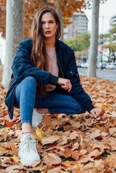 秋の公園でカメラにポーズを長い茶色の髪と青いジャケットの若くて魅力的な女の子。