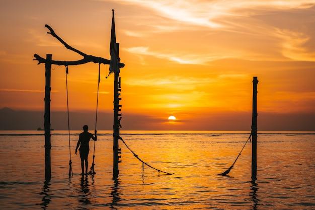 赤い空とインドネシアの有名なスイングでギリ島で最高の夕日の風景