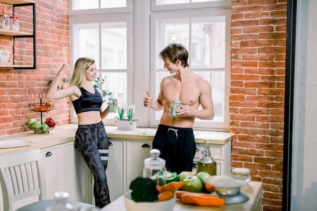 Здоровое питание, фитнес-образ жизни, правильное питание. молодая пара в черной спортивной одежде пьет зеленый коктейль на кухне у себя дома, симпатичная девушка сгибает бицепс