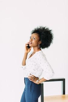 Веселая молодая афро-американская деловая женщина разговаривает по мобильному телефону, стоя возле современного стула, изолированных на белом