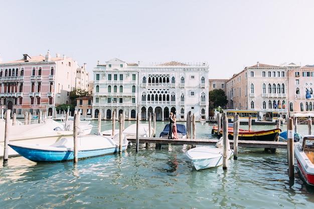 愛の美しいカップルは、ボートでヴェネツィアの運河の木製の橋の上に立ちます。イタリア、ベニス