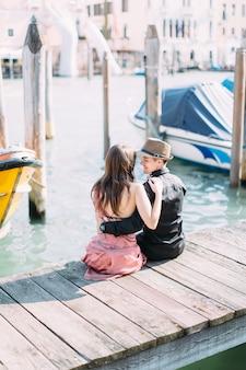 ヴェネツィアでの愛。イタリア、ヴェネツィアの運河のボートの間で木製の橋の上に座って素敵なカップルの素晴らしい写真