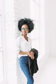 メガネ、大きな窓の近くに立って、ジャケットを保持している若いアフリカ系アメリカ人ビジネス女性