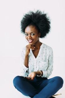 Молодая афро-американская бизнес-леди используя таблетку пока сидящ на поле, изолированном на белизне