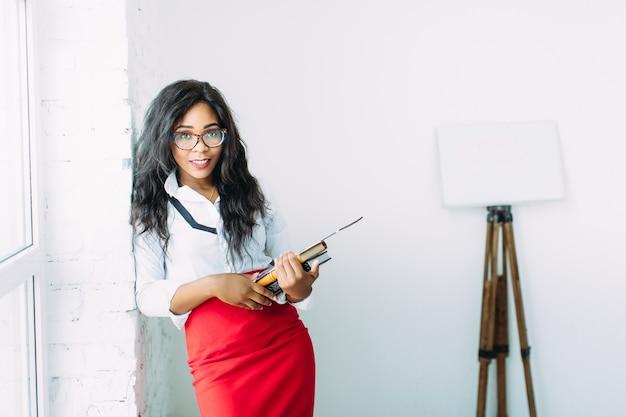 Афро-американский бизнес-учитель в очках, держа книги и документы, стоя у большого окна
