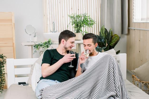 自宅でワインのグラスとベッドに横になっている幸せなゲイのカップル。同性愛者のカップルが抱き合って、ベッドでキスします。ゲイのカップルの愛の家のコンセプト