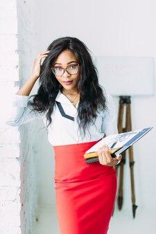 Афро-американская деловая женщина в очках держит книги и документы