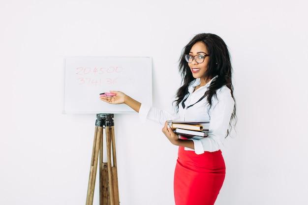 Красивая улыбающаяся учительница держит документы, книги, стоит возле доски