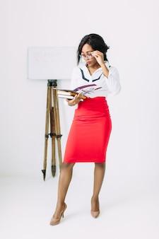 Красивая молодая учительница в белой рубашке и красной юбке держит книги и документы