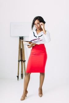 本やドキュメントを保持している白いシャツで美しい若いアフリカ教師