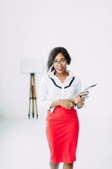 本や文書を保持している白いシャツで美しい若い笑顔の女性