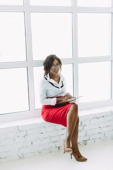 窓の近くに座っているアフリカ系アメリカ人のビジネス女性