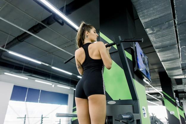 スポーツ、フィットネス、ライフスタイル、人々の概念-女性運動とジムで後ろからプルアップを行う