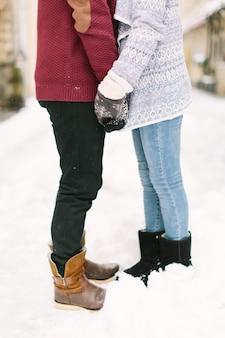 Счастливая и романтичная кавказская пара в теплых свитерах, идущих в зимнем городе львов. праздники, зима, любовь, горячие напитки, люди