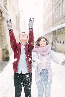 愛する若いカップルは雪で遊んで、朝の冬の街を歩く