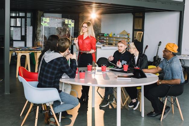 創造的な若い実業家は、オフィスで働いている同僚と付箋でガラスオフィスの壁でスピーチをしています