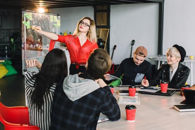 Многорасовых молодых творческих людей в современном офисе. группа молодых деловых людей работают вместе с ноутбуком, планшетом, смартфоном, ноутбуком. успешная хипстерская команда в коворкинге. фрилансеры.