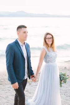 青いジャケットの新郎と豪華な青いドレスの花嫁の美しい幸せな結婚式のカップルは、ガルダ湖の近くに手をつないで歩いています。イタリア、シルミオーネ