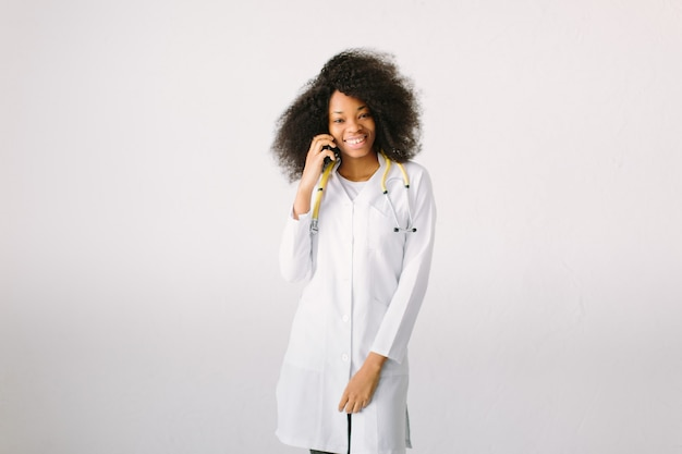 女医準備医療機器。白い背景の上の病院で聴診器で電話で話している女性医師