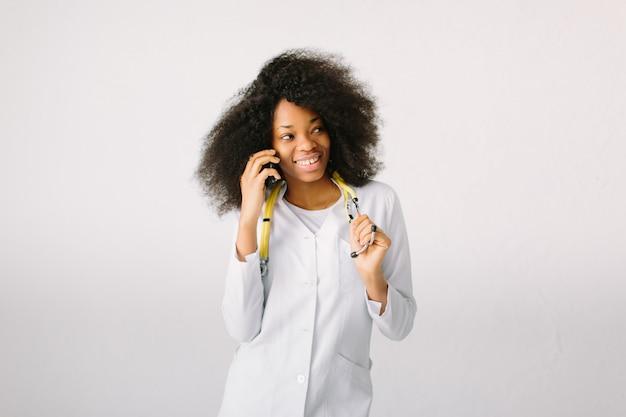 白い背景の上の病院で聴診器で電話で話している制服を着た若いアフリカ医師の肖像画
