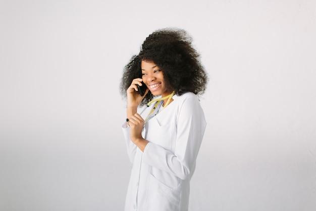 白い背景の上の病院で聴診器と電話で話しているスタジオで幸せなアフリカの医療インターン医師