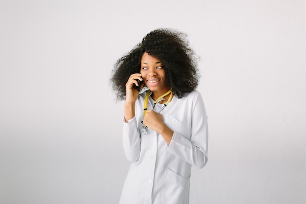 薬の広告デザイン。聴診器と病院内のフォルダーと白衣のアフリカ系アメリカ人の女の子の美しい少女。人間味のない幅広い背景。電話で話す