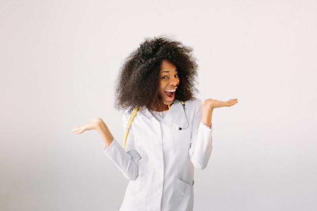 聴診器で白衣の美しい少女医師。白い背景の上