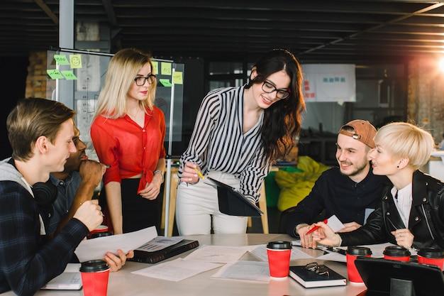 近代的なオフィスの多民族の若い創造的な人々。若いビジネス人々のグループは、ラップトップ、タブレット、スマートフォン、ノートブックと一緒に働いています。コワーキングで成功した流行に敏感なチーム。フリーランサー。