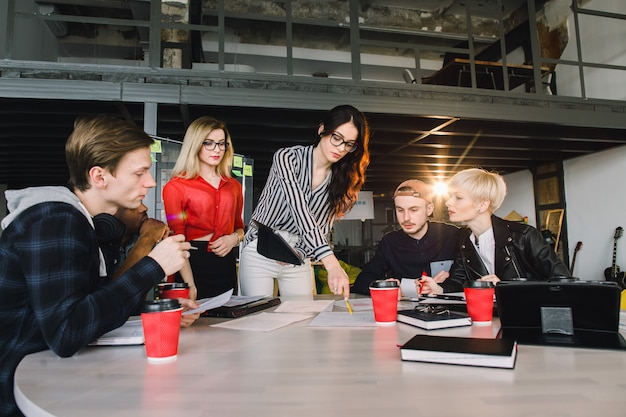 建築家の設計に従事する非公式の会議でテクノロジーを使用する若いビジネス専門家のチーム。大学図書館で一緒に学ぶ留学生。成功したスタートアップの概念