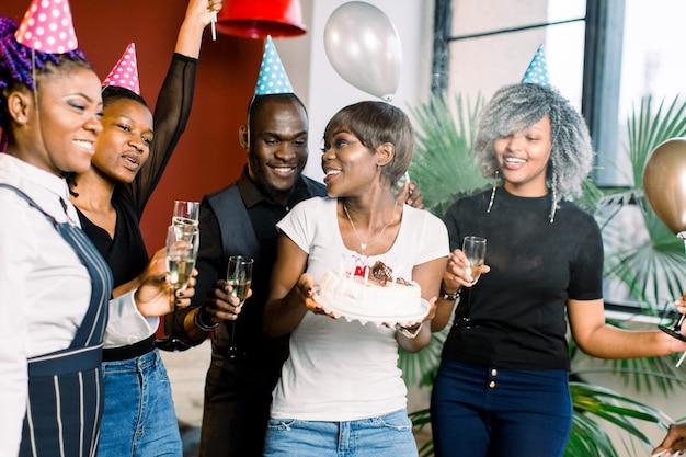 Веселая молодая африканская компания празднует день рождения и имеет торт со свечами