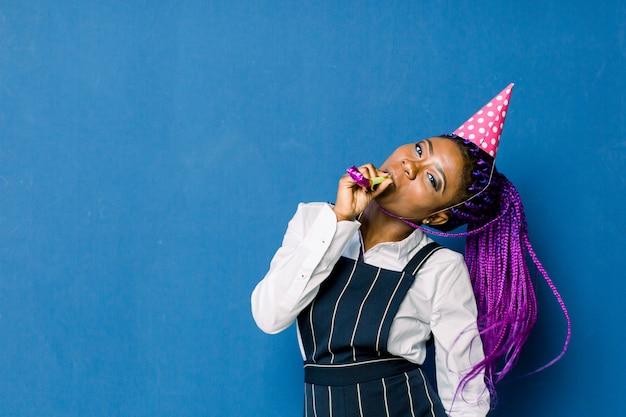 誕生日パーティー、新年のカーニバル。明るいイベントを祝う青い空間で若い笑顔のアフリカ女性は、鳴り物入りのピンクのパーティーハットで、エレガントなファッションの白いスカートと黒のパンツを着ています。
