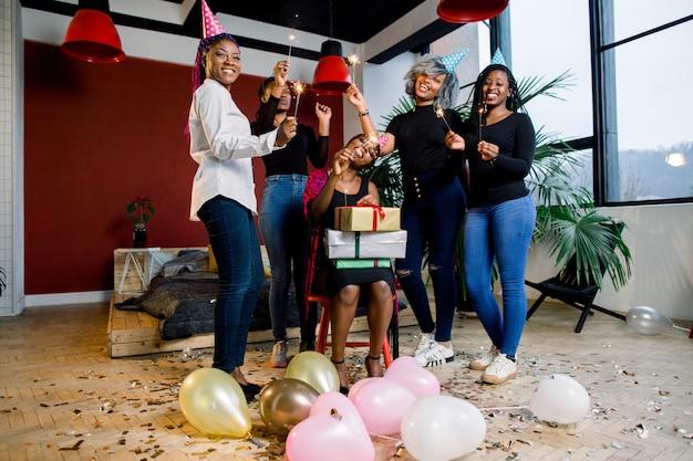 Африканские друзья празднуют день рождения и держат бенгальские огни и шляпы и подарки