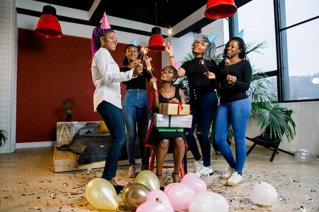 Красивая улыбающаяся африканская девушка держит подарки в руках и празднует день рождения с друзьями. девушки держат в руках бенгальские огни