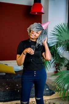 С днем рождения. девушка с конфетти и шампанское на вечеринке. портрет красивой усмехаясь африканской женщины в шляпе дня рождения держа шампанское в руках, празднуя праздник. высокое разрешение.