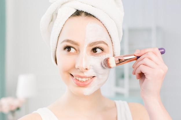シャワーの後お風呂タオルで肌を洗う若い美しい女性は、化粧ブラシで顔に粘土マスクを適用します。美容、健康、美容のコンセプトです。ライフスタイル。スキンケア