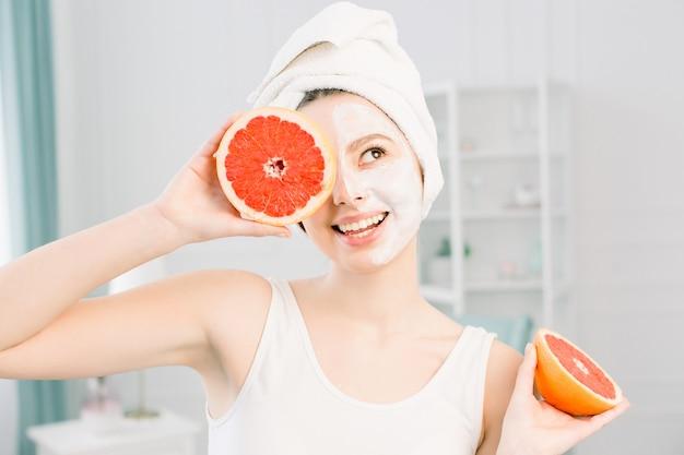 Портрет улыбающейся симпатичной девушки с белым полотенцем на голове, держащей половинки грейпфрута возле лица, закрывающего один глаз, здоровая идеально гладкая кожа, белая маска на одной половине лица, на светлом пространстве
