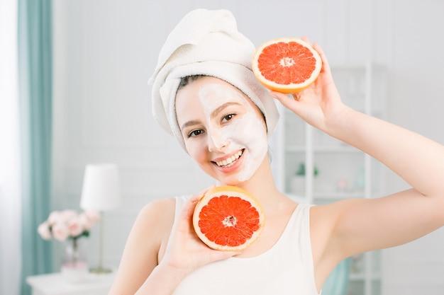 Красивая молодая женщина кавказа с белой очищающей маской на половине лица и грейпфрутовых половинок на светлом пространстве. натуральная косметика, уход за кожей, оздоровительный, уход за лицом, концепция косметологии.