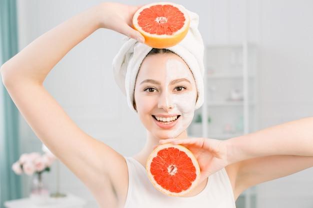 Конец вверх по женщине красоты с совершенной обнажённой кожей составляет грейпфрут владением изолированный на светлом космосе, портрете студии. концепция косметических процедур здравоохранения. макет копии пространства