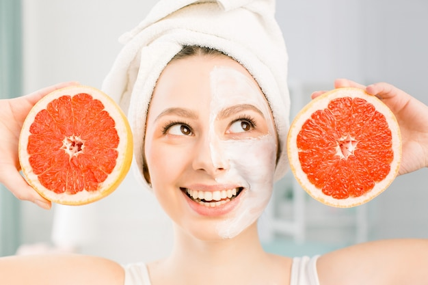 Красивая молодая женщина с белой маски лица и грейпфрута пополам на светлом пространстве. счастливая женщина с белым полотенцем на голове держит грейпфрут в руке