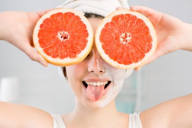 Молодая жизнерадостная европейская женщина с белой лицевой маской и белым полотенцем на голове показывает язык и держит большие грейпфруты, прикрывая глаза. здоровое питание, уход за кожей, уход за лицом, концепция косметологии.